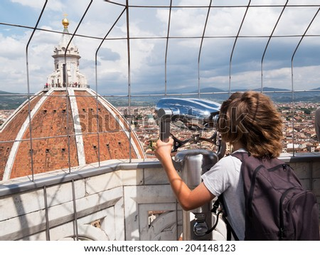 Tourism concept: boy looking through a sightseeing binoculars the Dome of Basilica di Santa Maria del Fiore (Saint Mary of the Flower), Florence, Tuscany, Italy, Europe. - stock photo