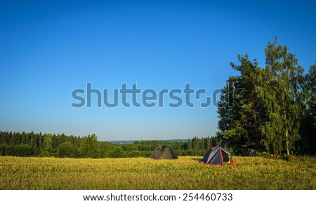 tourism concept: camp tents on the field - stock photo