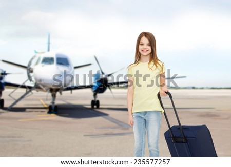 tourism, holiday, vacation, childhood and transportation concept - smiling little girl with travel bag over airport background - stock photo
