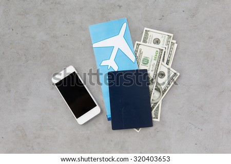 tourism, travel and objects concept - air ticket, money, smartphone and passport over gray concrete background - stock photo