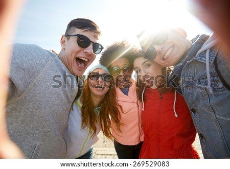 tourism, travel, people, leisure and technology concept - group of happy laughing teenage friends taking selfie outdoors - stock photo