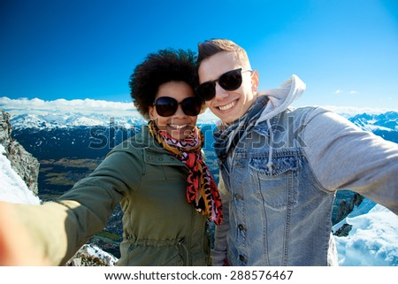 tourism, travel, people, leisure and technology concept - happy international teenage couple taking selfie over alps mountains in austria background - stock photo