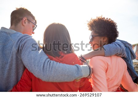 tourism, travel, people, leisure and teenage concept - group of happy friends hugging and talking on city street from back - stock photo