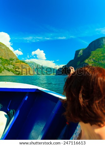 Tourism vacation and travel. Woman tourist taking photo with camera, view from deck of ship on fjord Sognefjord in Norway, Scandinavia. - stock photo