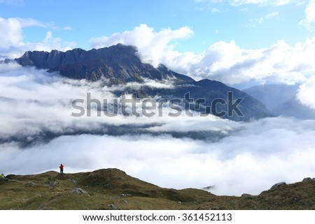 Tourist admiring the magnificent view of alpine mountains surrounded by sea of clouds ~ Scenery of awesome Tyrolean mountains in Lermoos, Tirol, Austria - stock photo