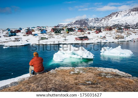 Tourist admiring wonderful views of Qeqertarsuaq, small town of Greenland in early spring time  - stock photo