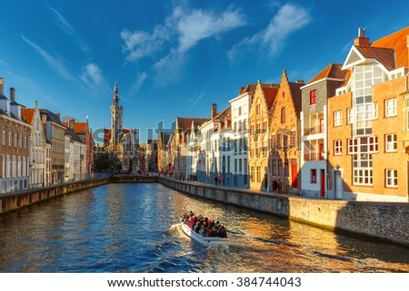 Tourist boat on canal Spiegelrei and Jan Van Eyck Square in the morning in Bruges, Belgium - stock photo