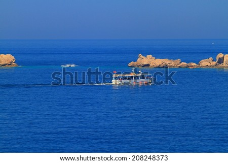 Tourist boat on the Adriatic sea near rocky islands - stock photo