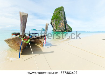 Tourist boats floating on the stunning tropical sea at scenic Railey Bay, Krabi, Southern Thailand. - stock photo