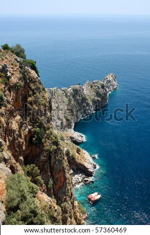 Tourist boats in blue water at a rock cape near Alanya Turkey - stock photo