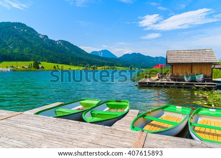 Tourist boats on shore of Weissensee lake in summer landscape of Alps Mountains, Austria - stock photo