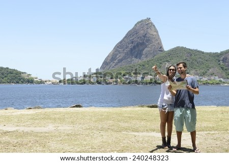 Tourist couple in Rio de Janeiro in front of the Sugarloaf Mountain, Brazil - stock photo