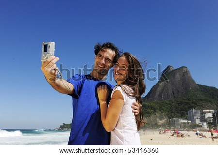 tourist couple in Rio de Janeiro taking a photo with a digital compact camera - stock photo