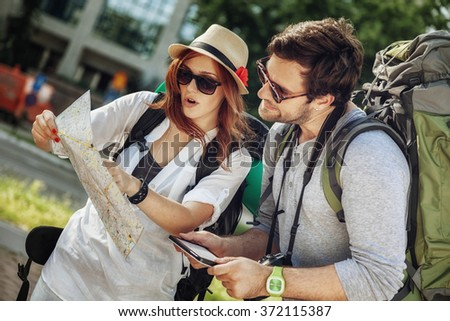 Tourist Couple In The City Browsing Map Using Digital Tablet - stock photo