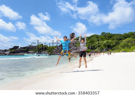 Tourist couple jumping for happy on beach near the sea under the blue sky and cloud of summer at Koh Similan Island in Mu Ko Similan National Park, Phang Nga province, Thailand - stock photo