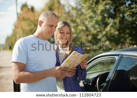 tourist couple looking at the map on the road. Focus on woman - stock photo