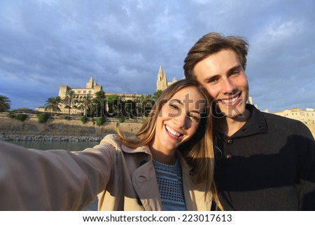 Tourist couple on holidays photographing a selfie with Palma de Mallorca Cathedral in the background - stock photo