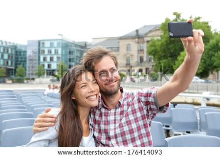 Tourist couple on travel in Berlin, Germany on boat tour cruise smiling happy taking selfie self-portrait photo picture while enjoying their romantic Europe travel vacation. Asian woman, Caucasian man - stock photo