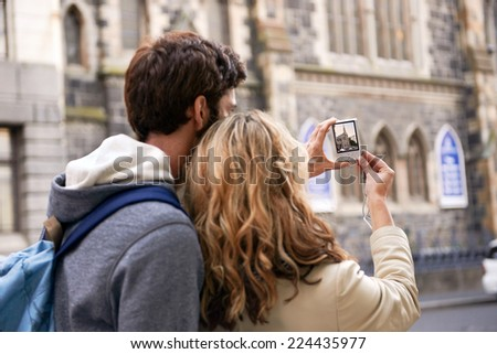 tourist couple taking photo of old historical church on holiday - stock photo