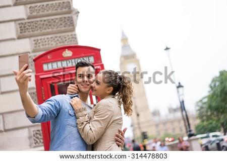 Tourist Couple taking selfie at Big Ben, London - stock photo
