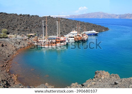 Tourist excursion boats at small port on volcano of Santorini  - stock photo