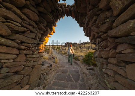Tourist exploring Inca trails at sunset on Amantani' Island, Titicaca Lake, among the most scenic travel destination in Peru. Travel adventures and vacations in the Americas. - stock photo
