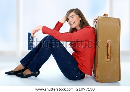 Tourist girl sitting on a suitcase with a ticket in her hand - stock photo