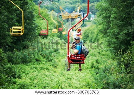Tourist going on Cable car funicular from the mountain Kizilovka to the lake in Atazhukinsky garden in Nalchik - stock photo