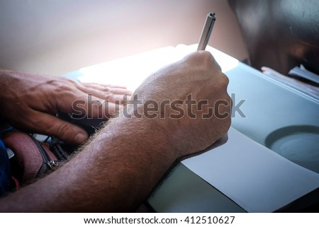 Tourist Hand Filling Custom Immigration Form on flight to visit country - stock photo