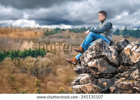 Tourist hiker man sitting on the rock in mountain - stock photo