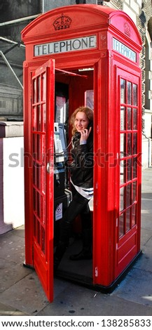 Tourist in a typical red telephone box in London - stock photo