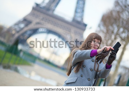 Tourist in Paris taking a picture of herself with Eiffel tower - stock photo