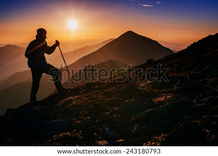 tourist in the mountains at sunset - stock photo