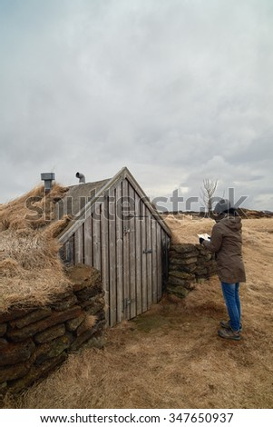 Tourist looking at traditional turf house in iceland - stock photo