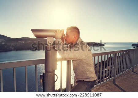 tourist looking through telescope - stock photo
