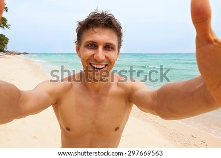 Tourist man beach taking selfie photo picture happy smile using smart phone summer vacation ocean paradise island travel  - stock photo
