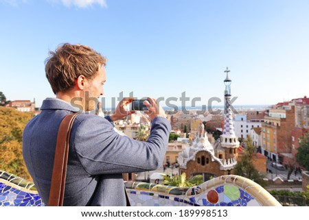 Tourist man taking photo in with smartphone in Park Guell, Barcelona, Spain. Young professional business man sightseeing taking picture with smart phone in Spain, Europe. - stock photo