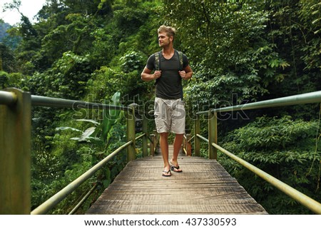 Tourist Man With Backpack Standing On Bridge And Enjoying Nature In Green Jungle Forest. Handsome Young Male Traveler Traveling On Summer Vacation. Travel And Tourism Concept.  - stock photo