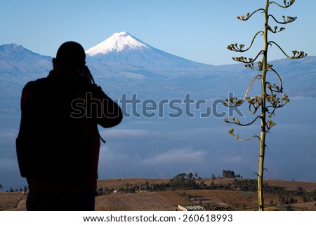 Tourist observing majestic Cotopaxi volcano in Ecuador, one of the highest active volcanoes in the world - stock photo