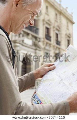 Tourist on Granada street Reading Map, side view - stock photo