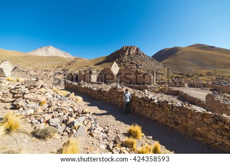 Tourist on the highlands of the Andes on the way to the famous Uyuni Salt Flat, among the most important travel destination in Bolivia. Abandoned and ruined old colonial village. - stock photo
