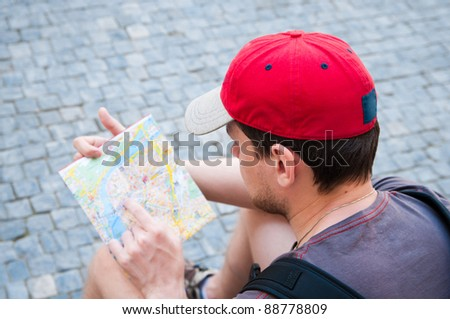 Tourist on the street looking at a guide - stock photo