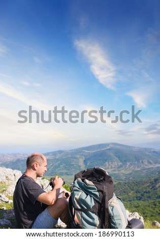 tourist on top of a mountain takes a snapshot of the nature - stock photo
