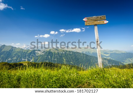 Tourist paths directions and travel time shown on a traditional direction signs at the Dolomites mountains, Italy  - stock photo