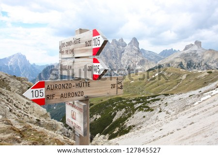tourist paths directions and travel time shown on a traditional direction signs at the Dolomiti mountains, Italy - stock photo
