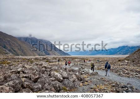 Tourist People walking in Tasman Glacier Valley, New Zealand - stock photo