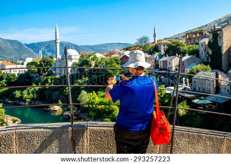 Tourist photographing city view standing on the bridge in Mostar city in Bosnia and Herzegovina - stock photo