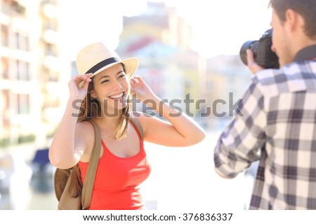 Tourist photographing his girlfriend wearing red shirt in a travel destination on vacations - stock photo
