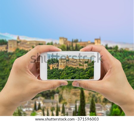 tourist photographing with a smartphone the ancient arabic fortress of Alhambra in Granada Spain Europe - stock photo