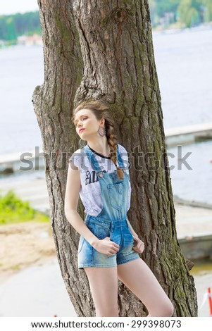 tourist pretty woman with trendy casual summer clothes posing with relaxed expression in sunny day near big tree with blue water of lake on background  - stock photo